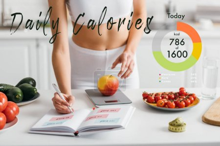Photo for Cropped view of fit sportswoman writing calories while weighing apple on kitchen table, daily calories illustration - Royalty Free Image