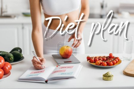 Photo for Cropped view of fit sportswoman writing calories while weighing apple on kitchen table, diet plan illustration - Royalty Free Image