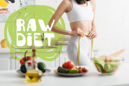 Photo for Selective focus of slim woman measuring waist with tape near fresh vegetables and salad on table, raw diet illustration - Royalty Free Image