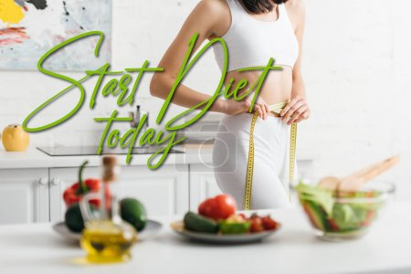 Photo for Selective focus of slim woman measuring waist with tape near fresh vegetables and salad on table, start diet today illustration - Royalty Free Image