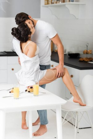 Photo pour Side view of man kissing and holding by leg sexy woman in bra and shirt near breakfast on table in kitchen - image libre de droit