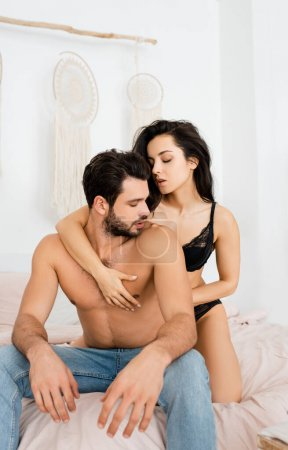 Photo pour Sexy woman in underwear touching chest of muscular boyfriend on bed - image libre de droit