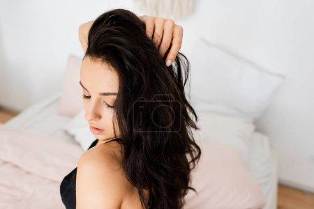 Photo pour Beautiful woman in bra touching hair on bed - image libre de droit