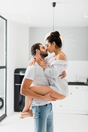 Photo pour Side view of handsome man holding in hands and kissing sexy girlfriend in kitchen - image libre de droit