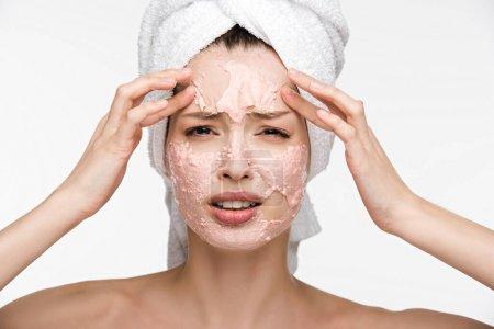 Photo pour Mécontent fille avec peeling visage masque facial toucher et regarder caméra isolé sur blanc - image libre de droit