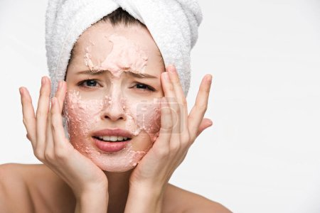 displeased girl with peeling facial mask touching face and looking at camera isolated on white