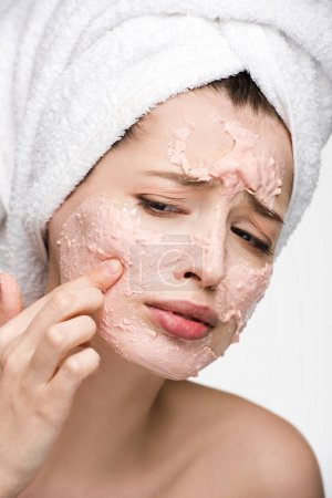 displeased girl with peeling facial mask touching face isolated on white