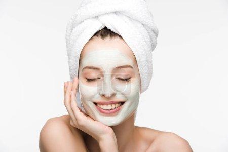 Photo pour Jolie fille avec masque nourrissant et serviette sur la tête touchant le visage avec les yeux fermés isolés sur blanc - image libre de droit