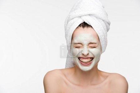 Photo pour Excitée fille avec masque nourrissant le visage et serviette sur la tête rire avec les yeux fermés isolés sur blanc - image libre de droit