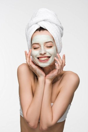 Photo for Cheerful girl with nourishing facial mask and towel on head touching face with closed eyes isolated on white - Royalty Free Image