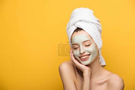 Foto de Chica feliz con máscara facial nutritiva tocando cara con los ojos cerrados aislados en amarillo. - Imagen libre de derechos