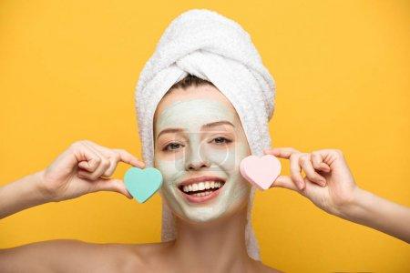 Photo pour Fille souriante avec masque nourrissant sur le visage tenant éponges cosmétiques en forme de coeur sur fond jaune - image libre de droit