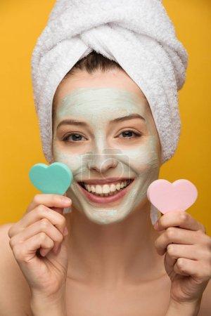 Photo pour Fille gaie avec masque nourrissant sur le visage tenant éponges cosmétiques en forme de coeur isolé sur jaune - image libre de droit