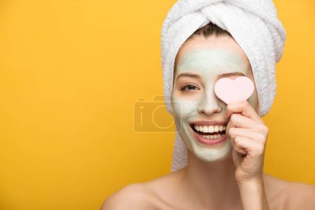 Photo for Cheerful girl with nourishing facial mask covering eyes with heart-shaped cosmetic sponge isolated on yellow - Royalty Free Image