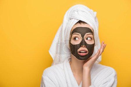 Photo pour Fille surprise avec masque d'argile faciale et serviette sur la tête tenant la main près du visage isolé sur jaune - image libre de droit