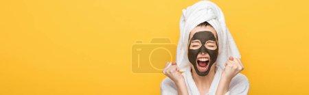 Photo pour Plan panoramique de fille en colère avec masque d'argile faciale et serviette sur la tête tenant les poings serrés et criant isolé sur jaune - image libre de droit