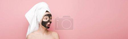 Photo pour Plan panoramique de fille choquée avec masque d'argile faciale et serviette sur la tête regardant loin isolé sur rose - image libre de droit