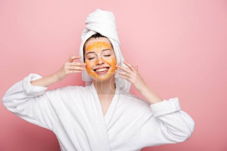 Photo for Smiling girl with citrus facial mask touching face with closed eyes on pink background - Royalty Free Image