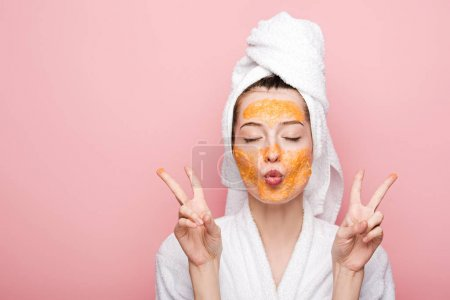 young woman with citrus facial mask showing victory gestures isolated on pink