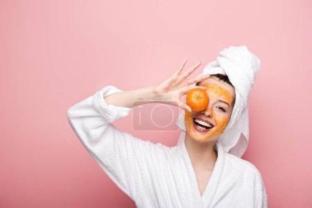 Photo pour Gaie fille avec des agrumes masque facial couvrant oeil avec mandarine sur fond rose - image libre de droit