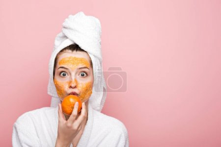 excited girl with citrus facial mask holding tangerine near mouth isolated on pink