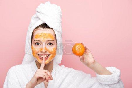 Photo pour Fille positive avec masque facial aux agrumes tenant la mandarine et montrant un geste de silence isolé sur rose - image libre de droit