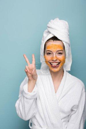 Photo pour Gaie fille avec des agrumes masque facial montrant geste de victoire tout en regardant la caméra sur fond bleu - image libre de droit