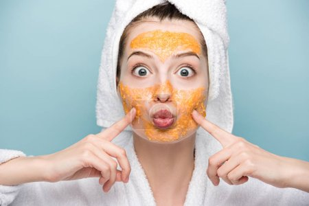 excited girl with citrus facial mask touching face while looking at camera isolated on blue