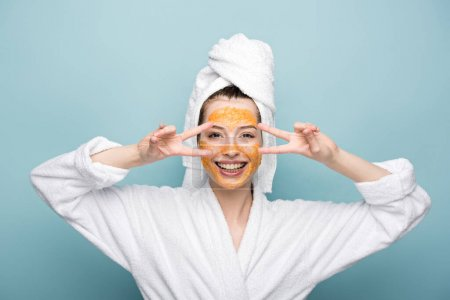 Photo for Cheerful girl with citrus facial mask showing victory gestures on blue background - Royalty Free Image