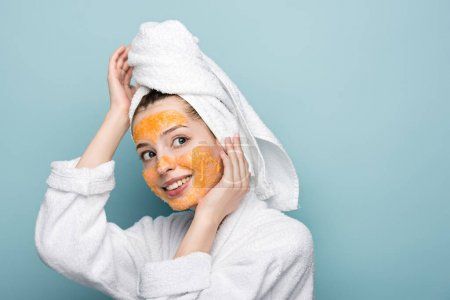 Photo for Smiling girl with citrus facial mask touching face and towel on head while looking away on blue background - Royalty Free Image