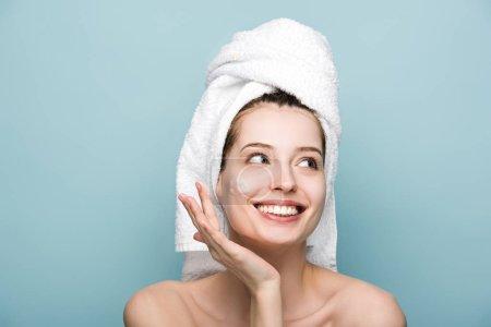 Photo pour Heureux attrayant fille appliquant hydratant masque facial tout en regardant loin isolé sur bleu - image libre de droit