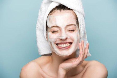 Photo pour Petite fille heureuse avec masque hydratant touchant le visage avec les yeux fermés isolée sur bleu - image libre de droit