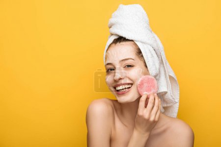 Photo for Happy girl with moisturizing facial mask looking at cosmetic sponge isolated on yellow - Royalty Free Image