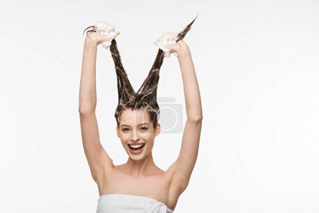 Photo pour Fille gaie s'amuser tout en lavant les cheveux longs isolés sur blanc - image libre de droit