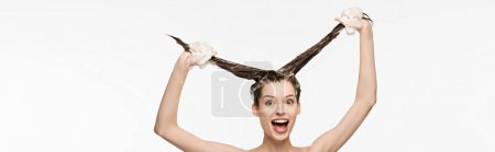 Photo for Panoramic shot of excited girl having fun while washing long hair isolated on white - Royalty Free Image