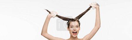 Foto de Foto panorámica de chicas emocionadas divirtiéndose mientras lavan el cabello largo aislado en blanco. - Imagen libre de derechos