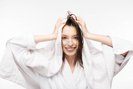 Photo for Happy girl wiping wet clean hair with white terry towel while smiling at camera isolated on white - Royalty Free Image