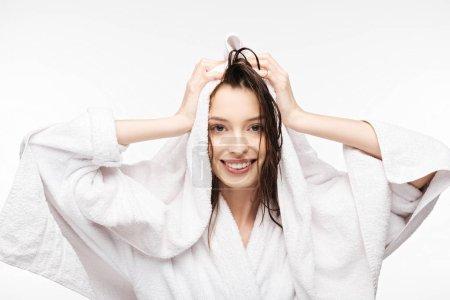 Photo pour Fille heureuse essuyant les cheveux propres humides avec une serviette éponge blanche tout en souriant à la caméra isolée sur blanc - image libre de droit