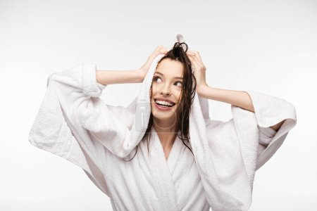 Photo for Happy girl wiping wet clean hair with white terry towel while looking away isolated on white - Royalty Free Image