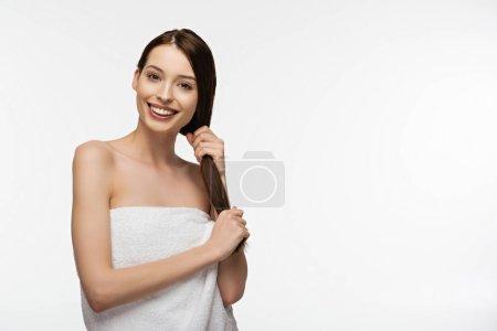 Photo pour Fille gaie toucher les cheveux longs et brillants tout en regardant la caméra isolée sur blanc - image libre de droit