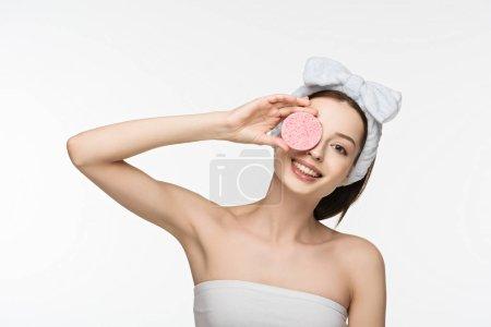 Photo pour Heureux fille couvrant oeil avec éponge cosmétique tout en regardant caméra isolée sur blanc - image libre de droit