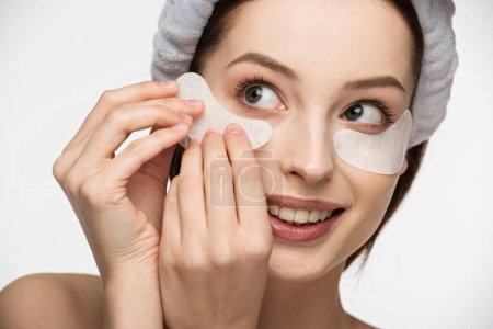 Photo pour Belle, fille souriante appliquant patch pour les yeux isolé sur blanc - image libre de droit