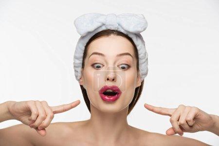 Photo pour Excité fille pointant avec les doigts à collagène patch sur les lèvres isolées sur blanc - image libre de droit