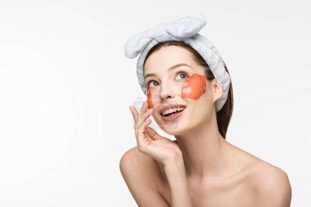 Photo pour Fille gaie avec des taches de collagène en forme de lèvre touchant le visage et regardant loin isolé sur blanc - image libre de droit