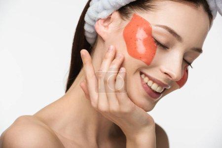 Photo pour Fille heureuse avec les yeux fermés toucher le visage avec patch collagène en forme de lèvre isolé sur blanc - image libre de droit