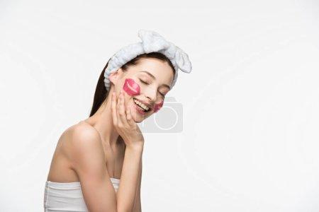 Photo pour Fille souriante avec des taches de collagène en forme de lèvre touchant visage isolé sur blanc - image libre de droit
