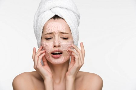 displeased girl with facial peeling mask touching face isolated on white