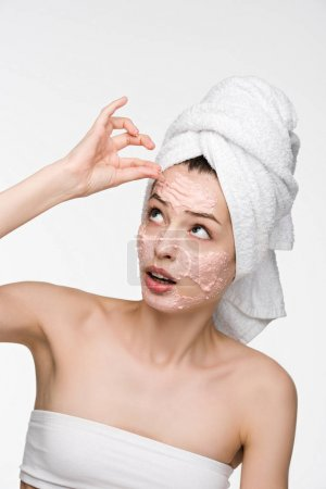 dissatisfied girl removing scrab mask from face while looking at camera isolated on white