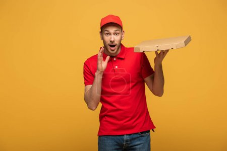 Photo for Happy delivery man in red uniform holding pizza box with open mouth isolated on yellow - Royalty Free Image