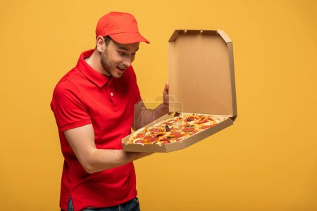 happy delivery man in red uniform looking at box with delicious pizza isolated on yellow